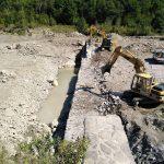 Escavatori a lavoro per la demolizione della briglia