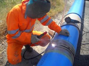 Saldatore realizza saldatura di giunzione tubi in acciaio dn500 per IREN, a Tressano, Reggio Emilia